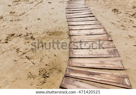 Wooden beach boardwalk, path with sand with copy space