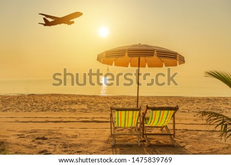 Wooden beach chairs and parasols on tropical sandy beach in the morning  with white passenger airplane landing above the sea , destinations relax summer holidays concept  #1475839769
