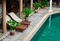 Wooden beach chairs beside indoor swimming pool.