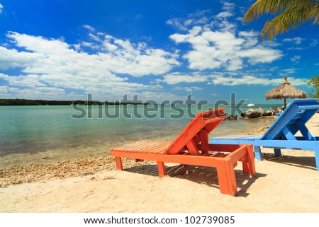Wooden beach lounge chairs along the shoreline of the Florida Keys with pretty blue sky and clouds and thatched hut in the background.