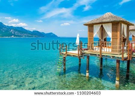 Wooden beach pavilions on the shore of a sandy beach - the Mediterranean coast, Beldibi, Antalya, Turkey