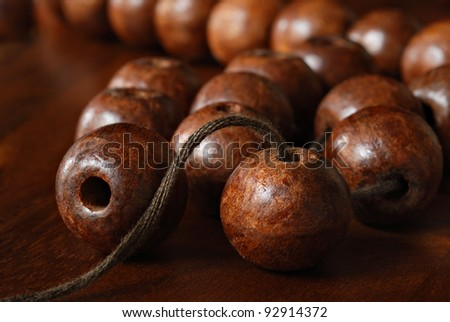 Wooden beads with twine for stringing together to create a necklace, home decor craft or simply as an educational activity.  Macro with shallow dof.  Selective focus limited to closest beads.