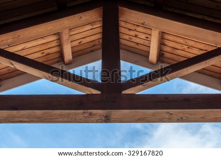 Wooden beam ceiling with symmetrical design. Modern art and design. Interior design with wood detail. Abstract minimal art. Blue sky background. Artistic design. geometrical balance and design.
