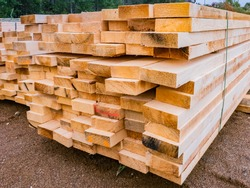 Wooden beams are fastened with clamps. Concept - lumber warehouse. Lumber is stored on the street. Concept - lumber for frame house. Wooden beams prepared for construction. Woodworking