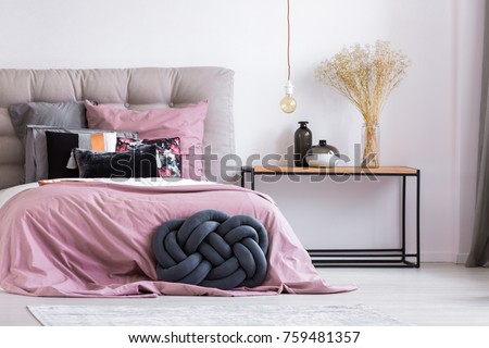 Wooden bedside table and blue handmade pillow next to bed with pink overlay in stylish apartment with simple bedroom decor