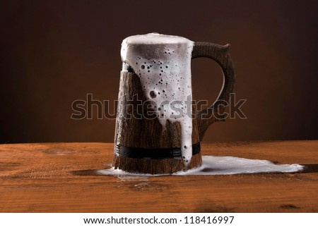 Wooden beer mug with foam on the dark red background.