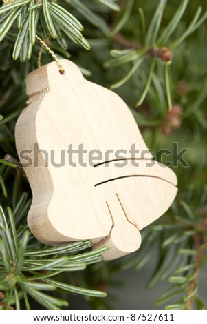 wooden bell decoration hanging on Christmas tree