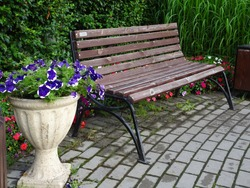 wooden bench and stone vase with flowers on a paved walkway