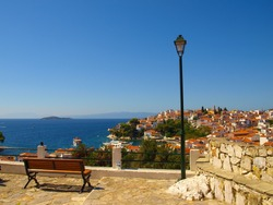Wooden bench and street lamp with panoramic view over The Aegean Sea and Skiathos, Greece