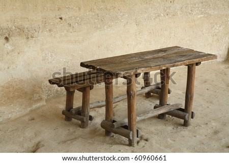 wooden bench and table on stone floor and wall