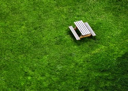 Wooden bench and table on the green grasses of a park