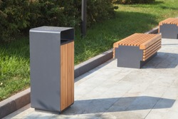 Wooden bench and trash can in the city park. Modern urban style of public place.