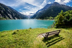 wooden bench at a reservoir in austria