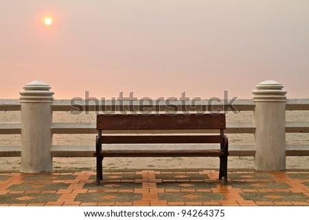 Wooden bench at the sea with sun in background