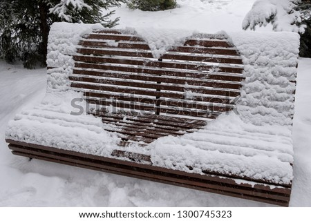Wooden bench covered with snow and heart drawn on it. Heart drawn on snow on bench in park. Saint Valentine's day. #1300745323