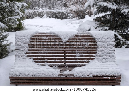 Wooden bench covered with snow and heart drawn on it. Heart drawn on snow on bench in park. Saint Valentine's day. #1300745326