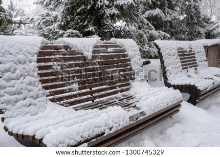 Wooden bench covered with snow and heart drawn on it. Heart drawn on snow on bench in park. Saint Valentine's day. #1300745329
