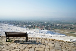 Wooden bench facing natural landscape and Thermal pools of Pamukkale (Cotton castle) mineral-rich thermal waters flowing down white travertine terraces on a nearby hillside- Denizli, Turkey