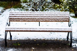 Wooden bench in the Park, covered with snow. Beginning of winter.