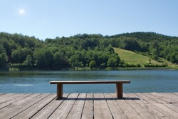 wooden bench looking at the lake and forest