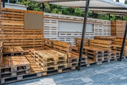Wooden bench made of pallets of freight cargo cases for sitting. Creative outdoor cafe table and benches. Conceptual chairs and tables. Modern urban loft design. Furniture from vintage boards.