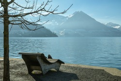 Wooden bench near Lake Lucerne in small village of Vitznau, Switzerland with beautiful landscape in the background. Ideal place to sit and relax
