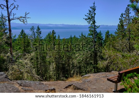 Wooden bench near summit of Mount Maguire provides views over forests of Sooke, BC and the strait of Juan de Fuca to Washington's Olympic Mountains Stock fotó ©