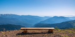Wooden bench on a mountain range. Beautiful natural landscape, summer mountain landscape over the mountain range with wooden bench and green wood in nature background.