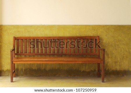 wooden bench on a yellow wall.