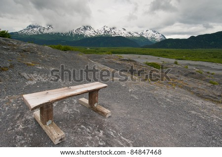 Wooden bench on mountain overlooking majestic landscape.