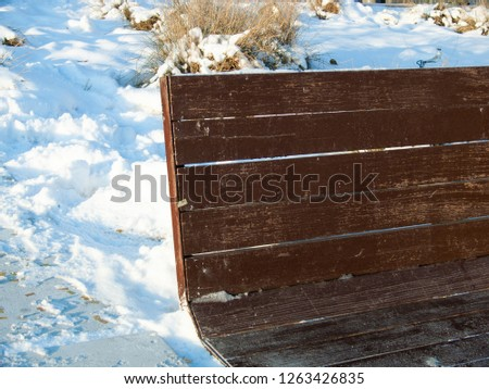 Wooden bench on snow background. Blue shadows on white snow abstract photo. Merry Christmas or Happy New Year wallpaper or postcard. Frozen ground surface. Winter seasonal banner. Christmas holiday