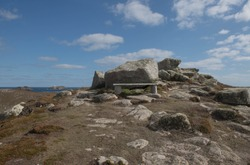 Wooden Bench on Top of a Cliff Surrounded by Granite Boulders with the Atlantic Ocean in the Background on the Island of Tresco in the Isles of Scilly, England, UK