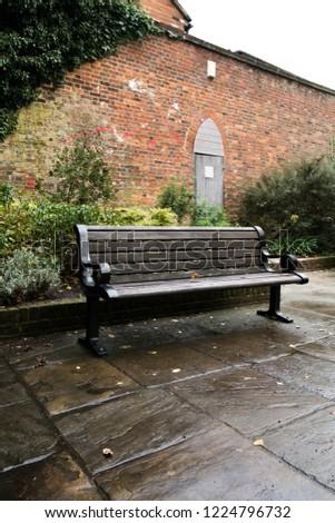 Wooden bench outside in a public area #1224796732