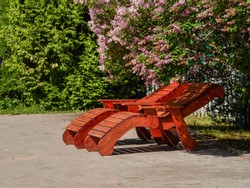 Wooden bench with metal art forging in the amusement park. Brown bench on the green background of nature.