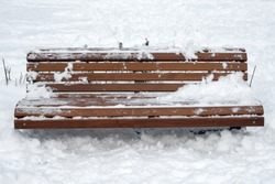 Wooden bench with snow in the park