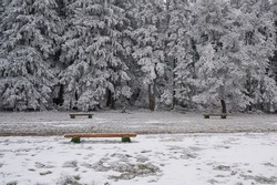 Wooden benches in an openair park in a winter day