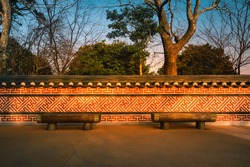 Wooden benches with Korean traditional walls at sunset in South Korea.