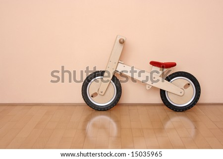 wooden bicycle leaning against a wall