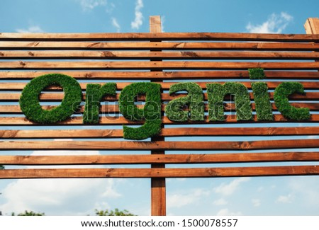Wooden billboard with the logo 100 % organic with leaves. Organic insiration . Organic icon. Natural product #1500078557