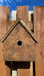 Wooden bird box on a rustic brown wooden slatted fence. blue sky in background