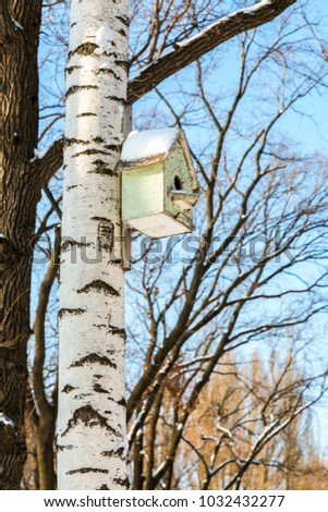 Wooden birdhouse on a birch tree in the winter park #1032432277