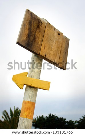 Wooden blank placard and arrow pointing left pinned to a post against s dull sky