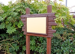 Wooden blank sign board in the green park