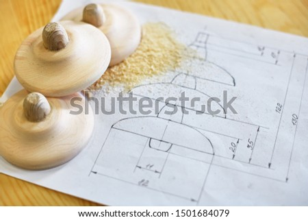 Wooden blanks are on paper with a drawing. Production of products in the carpentry workshop. #1501684079
