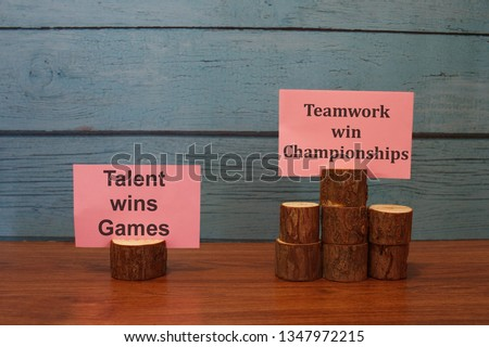 "Wooden block arranged with motivation note written ""Talent wins games & Teamwork win championships"" #1347972215"