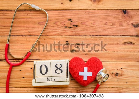 Wooden Block calendar for World Red Cross and Red Crescent day, May 8. Healthcare and medical concept. Red heart with Stethoscope on wooden table background texture.