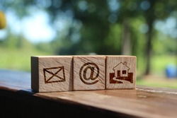 Wooden block cube symbol telephone, email, address and mobile phone. Website page contact us or e-mail marketing concept
