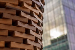 Wooden block sculpture contrasted with glass and metal building facade in Washington DC.