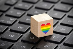 Wooden block with LGBT rainbow heart symbol of love 2d graphic illustration on laptop keyboard.