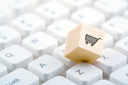 Wooden block with shopping cart graphic on computer keyboard. Online shopping concept.